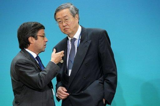 China's Zhou Xiaochuan (R) listens to president of the Inter-American Development Bank Luis Alberto Moreno (L)