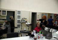 Employees at a hair salon wearing face masks to prevent the spread of coronavirus, work on customers in Athens, Monday, March 22, 2021. Greece's government reopened a limited number of barbershops and hair salons on Monday. (AP Photo/Thanassis Stavrakis)