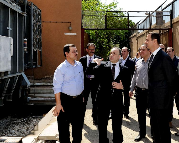 In this photo released by the Syrian official news agency SANA, President Bashar Assad, right, visits the Umayyad Electrical Station on May Day, a day after a powerful bomb hit the capital. in Damascus, Syria, Wednesday, May 1, 2013. (AP Photo/SANA)