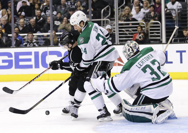 Dallas Stars' Jordie Benn, center, and Los Angeles Kings' Colin Fraser, left, fight for the puck in front of Dallas Stars goalie Kari Lehtonen, of Finland, during the second period of an NHL hockey game on Monday, Dec. 23, 2013, in Los Angeles. (AP Photo/Jae C. Hong)