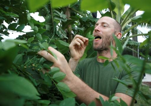 Rob Greenfield samples katuk, a leaf vegetable that he has grown in a home garden in Orlando