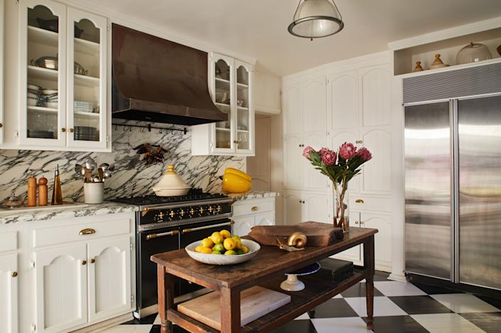 """<div class=""""caption""""> The kitchen in fashion and jewelry designer Ambre Dahan's L.A. home is a lesson in past meets present: A vintage table blends seamlessly with new Arabescato marble countertops (""""I went to the marble yard myself,"""" she says) and a <a href=""""https://www.lacanche.com/"""" rel=""""nofollow noopener"""" target=""""_blank"""" data-ylk=""""slk:Lacanche"""" class=""""link rapid-noclick-resp"""">Lacanche</a> range, which Dahan promises she uses regularly for her epic dinner parties, or for crab boils on her daughter's birthday. </div>"""