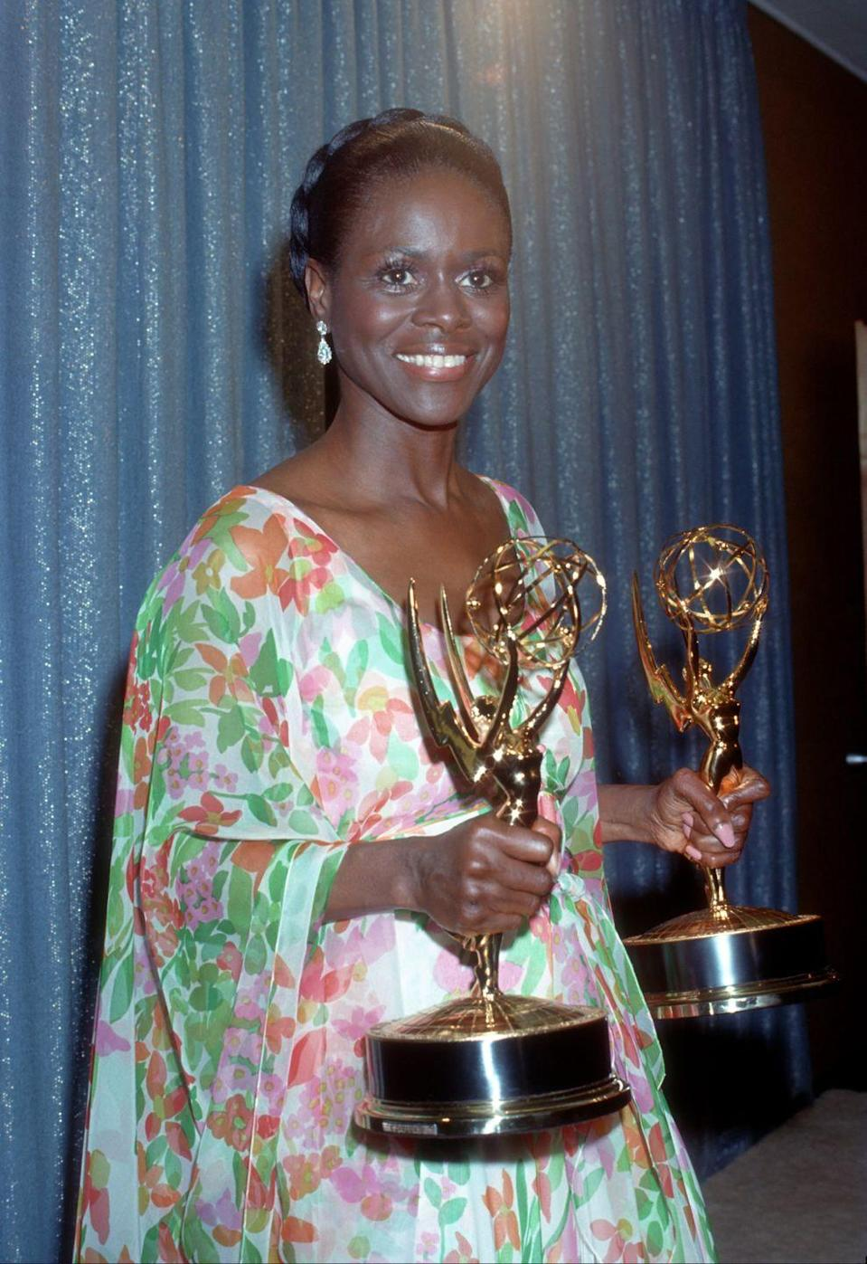 <p>Cicely Tyson holds the two Emmys she won for <em>The Autobiography of Jane Pittman</em> while wearing a beautiful scoop neck, floral printed dress, and braided crown bun.</p>
