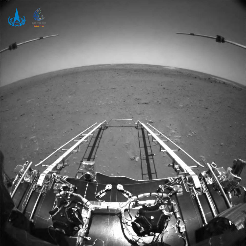 In this black and white photo taken by China's Zhurong Mars rover and made available by the China National Space Administration (CNSA) on Wednesday, May 19, 2021, extension arms and a departure ramp are deployed on the rover's lander on the surface of Mars. China landed a spacecraft on Mars for the first time on Saturday, a technically challenging feat more difficult than a moon landing, in the latest step forward for its ambitious goals in space. (CNSA via AP)