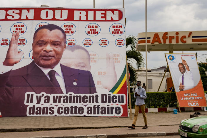 A man walks between election posters featuring opposition presidential candidate Guy Brice Parfait Kolelas, right, and President Denis Sassou N'Guesso, left, in central Brazzaville, Congo, Friday March 12, 2021. Elections on Sunday March 21 will see President Denis Sassou N'Guesso poised to extend his tenure as one of Africa's longest serving leaders, 36 years, amid opposition complaints of interference with their campaigns.(AP Photo/Lebon Chansard Ziavoula)