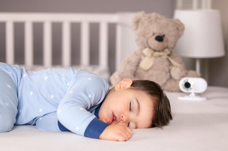 Cute little baby boy in light blue pajamas sleeping peacefully on bed at home with baby monitor camera and soft teddy bear toy at background. Child daytime sleeping schedule
