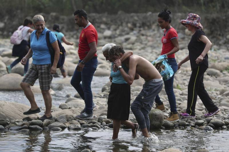 A youth helps an elderly woman walk across the Tachira River into Colombia as people are forced to cross the border illegally due to the closure of the Simon Bolivar International Bridge by Venezuelan authorities, in La Parada, near Cucuta, Colombia, Sunday, March 3, 2019. Last weekend, opposition leader Juan Guaido coordinated a failed effort to bring aid from Colombia and Brazil into Venezuela, where security forces loyal to President Nicolas Maduro blocked the supplies at its border bridges, with Maduro describing Guaido's gambit as part of a U.S.-backed plot to overthrow him. (AP Photo/Martin Mejia)