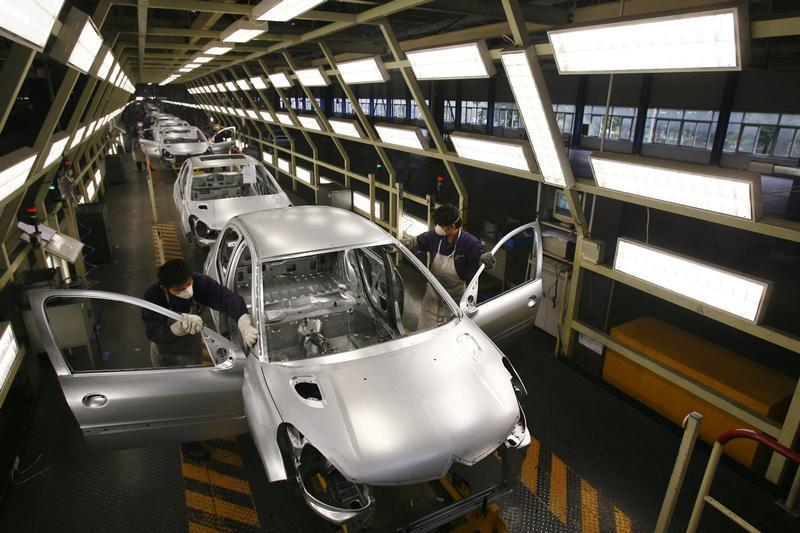 Peugeot employees work on the assembly line at the Dongfeng PSA Peugeot Citroen factory in Wuhan