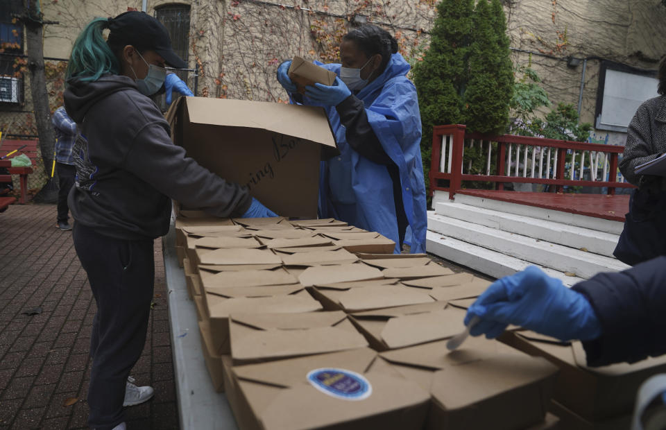 Volunteers unload boxed meals prepared at the South Bronx restaurant La Morada, Wednesday Oct. 28, 2020, in New York. After a fund raising campaign during the coronavirus pandemic, La Morada, an award winning Mexican restaurant, was reopened and now also functions as a soup kitchen, serving 650 meals daily. (AP Photo/Bebeto Matthews)