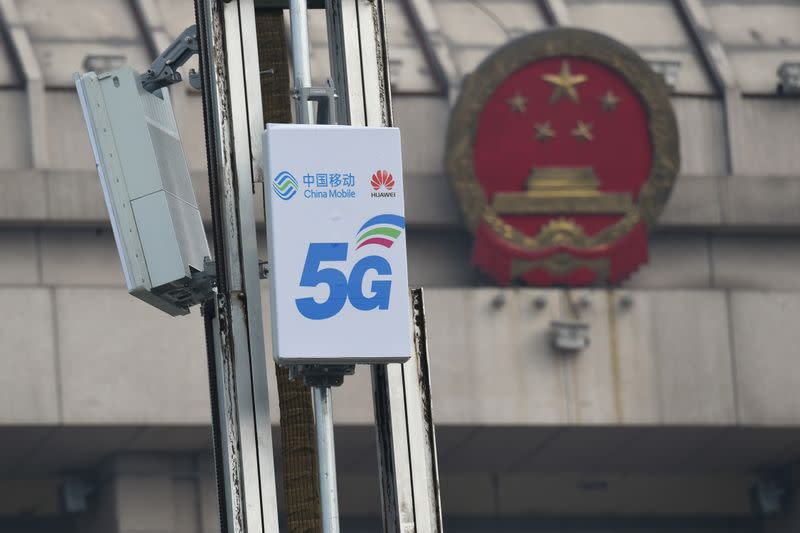 5G active antenna units with logos of China Mobile and Huawei are seen in front of a National People's Congress (NPC) conference center in Luoyang, Henan