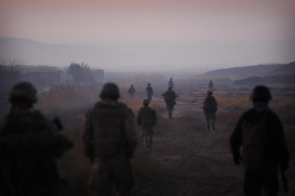 """United States Marines from the 2nd Battalion 2nd Marines """"Warlords"""" and Afghan National Army soldiers walk in formation during an operation in the Garmsir district of the volatile Helmand province, southern Afghanistan, Wednesday, Dec. 23, 2009. (AP Photo/Kevin Frayer,File)"""