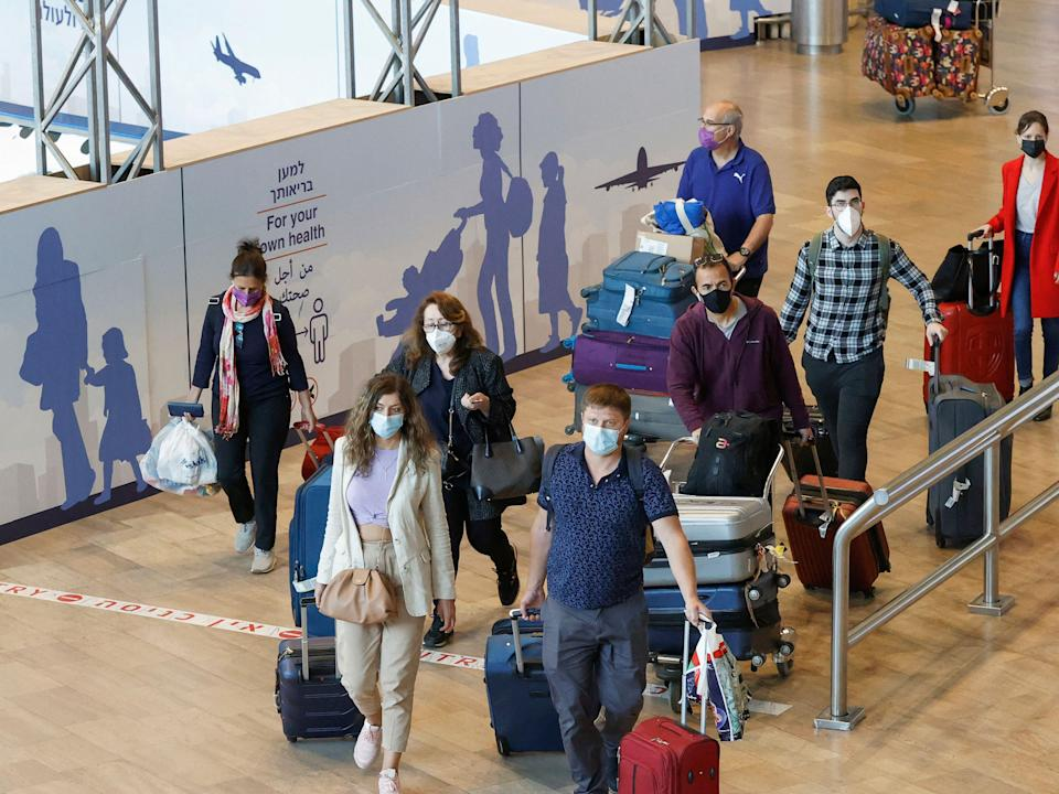 Israelis and vaccinated tourists wearing masks for COVID-19 protection arrive to Israel's Ben Gurion Airport near Tel Aviv on May 23, 2021, after a partial re-opening of the border to inoculated tourists from 14 countries.