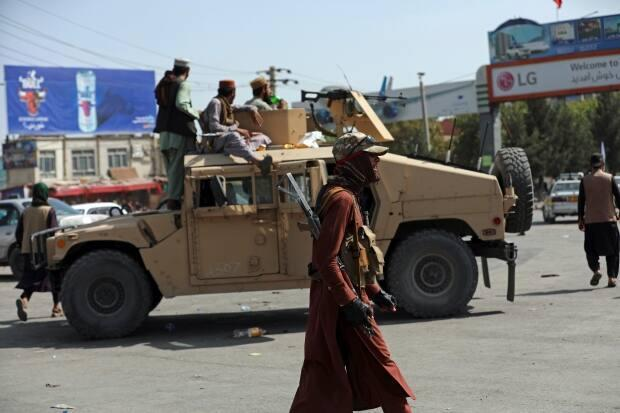 Taliban fighters stand guard in front of the Hamid Karzai International Airport, in Kabul on Monday. Thousands of people packed into the Afghan capital's airport, rushing the tarmac and pushing onto planes in desperate attempts to flee the country after the Taliban overthrew the Western-backed government.  (Rahmat Gul/The Associated Press - image credit)