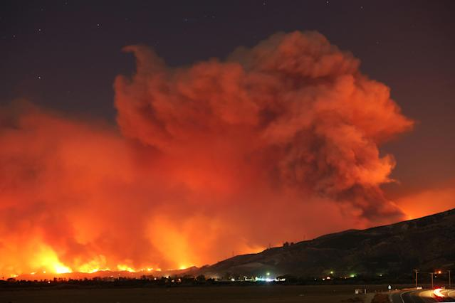 <p>Smoke rises into the night sky as strong winds push the Thomas Fire across thousands of acres near Santa Paula, Calif., Dec. 4, 2017. (Photo: David McNew/Reuters) </p>