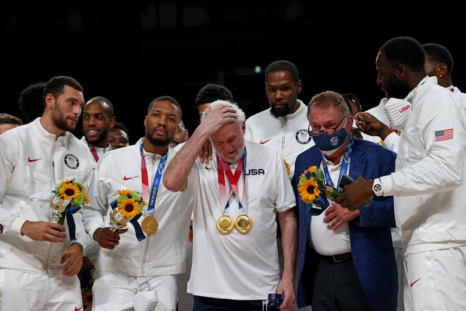 Tokyo 2020 Olympics - Basketball - Men - Medal Ceremony - Saitama Super Arena, Saitama, Japan - August 7, 2021. United States coach Gregg Popovich reacts as he stands with teammates at the podium REUTERS/Brian Snyder