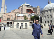"""Turkey's President Recep Tayyip Erdogan gestures as he arrives to speak to supporters and the media after Friday prayers in Hagia Sophia, in the background, in Istanbul, Friday, Aug. 7, 2020. Erdogan joined worshipers on July 24 for the first Muslim prayers in 86 years inside the Istanbul landmark that served as one of Christendom's most significant cathedrals, a mosque and a museum before its conversion back into a Muslim place of worship.Turkey's president has called a maritime deal between Greece and Egypt """"worthless,"""" saying Turkey will resume oil and gas exploration in the Eastern Mediterranean.(Turkish Presidency via AP, Pool)"""