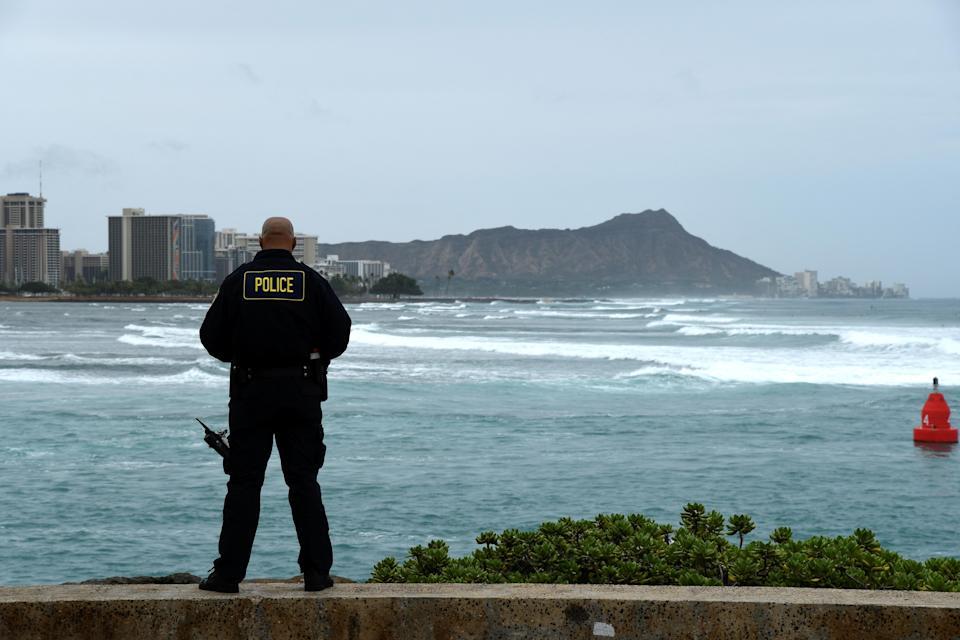 <p>Honolulu police officer Chad Asuncion monitors the water conditions and warns surfers about the conditions as Hurricane Lane approaches Honolulu, Hawaii, Aug. 23, 2018. (Photo: Hugh Gentry/Reuters) </p>