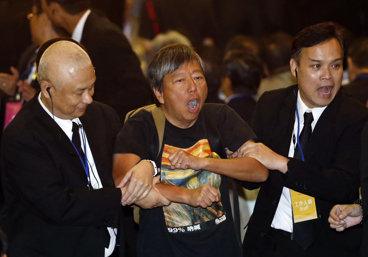 "Pro-democracy lawmaker Lee Cheuk Yan, center, is taken away by security guards after a protest against Li Fei, deputy secretary general of the National People's Congress' Standing Committee, in Hong Kong Monday, Sept. 1, 2014. China's legislature on Sunday ruled out allowing open nominations in the inaugural election for Hong Kong's leader, saying they would create a ""chaotic society."" Democracy activists in the Asian financial hub responded by saying that a long-threatened mass occupation of the heart of the city ""will definitely happen."" (AP Photo/Kin Cheung)"