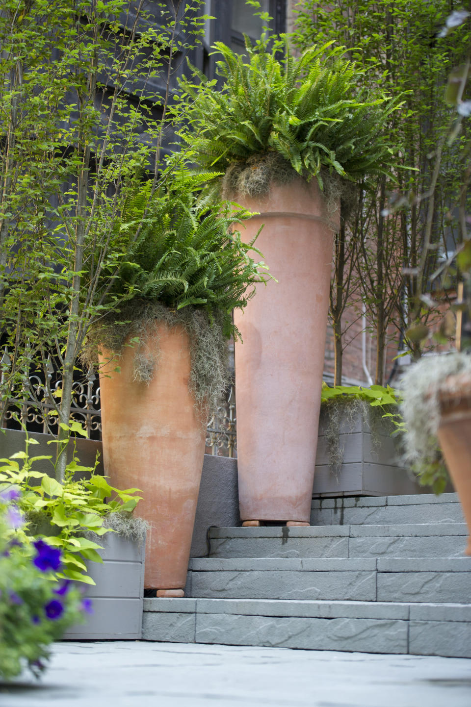 "Tall terra cotta planters add a 'wow' factor to this stoop, with landscaping design by Janice Parker. Front stoops have long welcomed visitors to city homes, and have served as gathering spots for friends and neighbors engaging in what urban design activist Jane Jacobs called ""the sidewalk ballet."" (Neil Landino Jr./Janice Parker Landscape Architects via AP)"