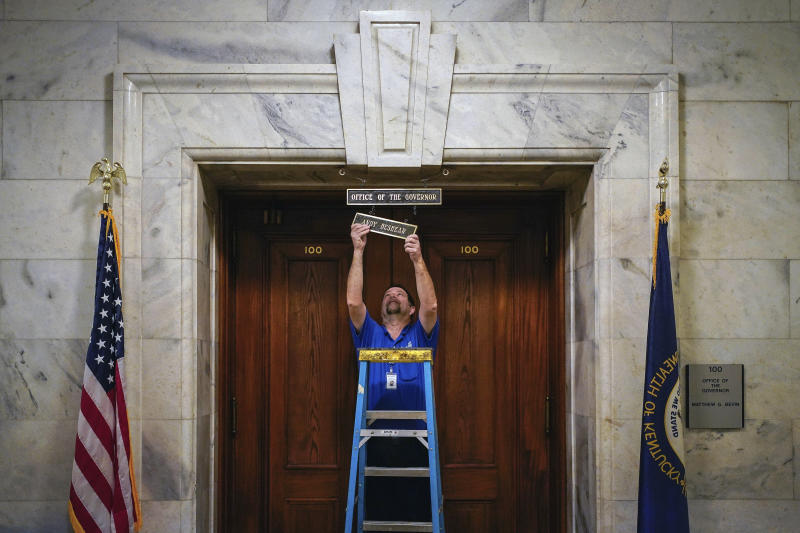 Joel Benowit, operations branch manager for finance facilities, hangs a name plaque for Kentucky's Democratic Gov. Andy Beshear over the Governor's Office in the Capitol Building shortly after his private swearing-in ceremony, early Tuesday, Dec. 10, 2019, in Frankfort, Ky. (Bryan Woolston/Pool Photo via AP)