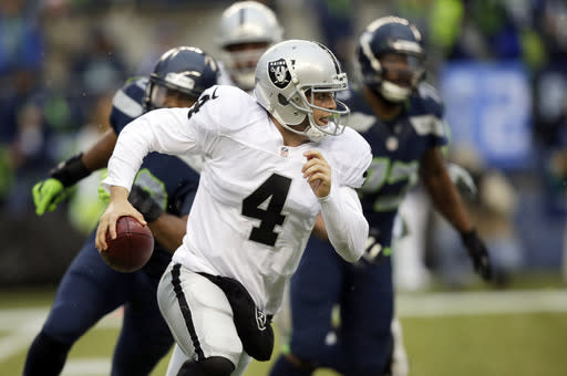 Oakland Raiders quarterback Derek Carr scrambles with the ball in the second half of an NFL football game against the Seattle Seahawks, Sunday, Nov. 2, 2014, in Seattle. (AP Photo/Stephen Brashear)
