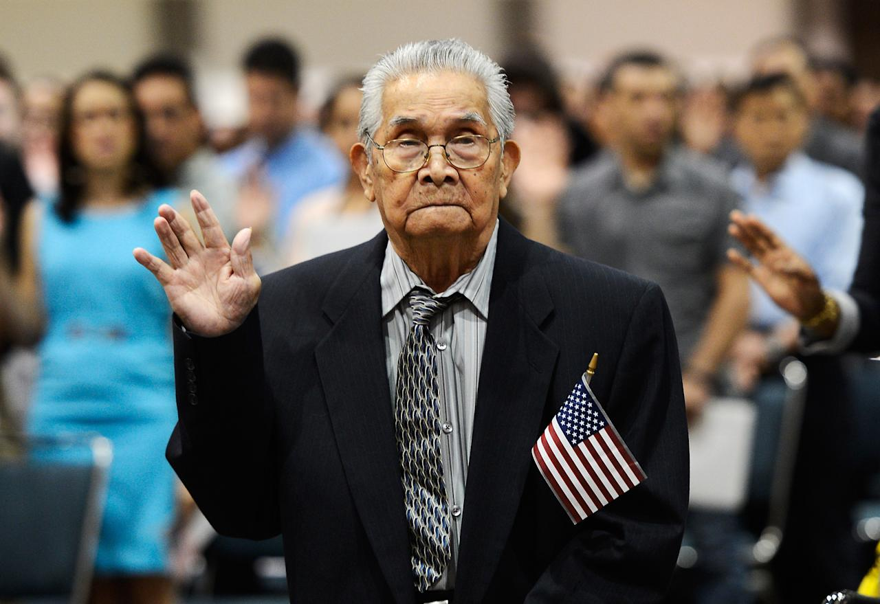 The oldest candidate to become a U.S. citizen 102 year-old Joaquin Arciago Guzman from the Philippines raises his arm to take the oath of citizenship at a naturalization ceremony at the Los Angeles Convention Center on June 27, 2012 in Los Angeles, California. More than 7,000 candidates became citizens representing more than 120 countries.  (Photo by Kevork Djansezian/Getty Images)