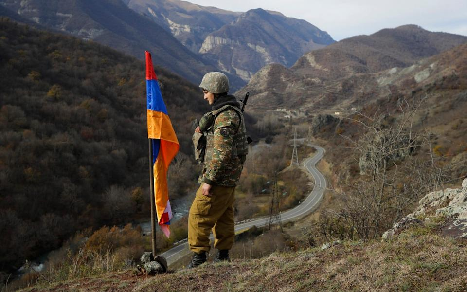 An ethnic Armenian soldier stands guard in Nagorno-Karabakh at a new border with Kalbajar district - Sergei Grits/AP