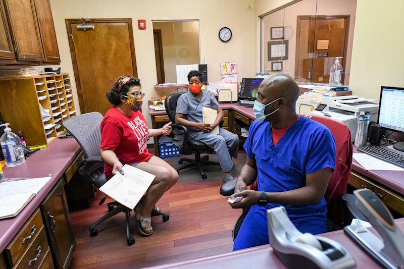 Amanda Reyes, center, talks with medical team manager Alesia Horton, left, and office manager Chadric Jackson in the front office at the West Alabama Women's Center on June 5 in Tuscaloosa. (Photo: Julie Bennett for HuffPost)