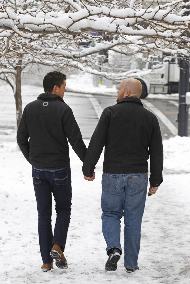 FILE - In this Saturday, Dec. 21, 2013, file photo, Jon Jensen, left, and his partner, Jared Reesor, walk away hand-in-hand from the Ogden clerk and auditor's office after it canceled a special Saturday opening to issue marriage licenses in Ogden, Utah. A day earlier, a federal judge struck down Utah's ban on same-sex marriage, saying the law violates the U.S. Constitution. (AP photo/George Frey, File)