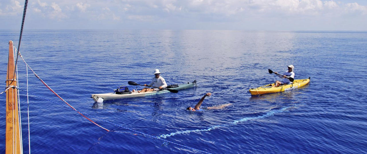 In this photo provided by Diana Nyad via the Florida Keys News Bureau, endurance swimmer Diana Nyad swims in the Florida Straits between Cuba and the Florida Keys Sunday, Aug. 19, 2012, escorted by support personnel in kayaks. Nyad is endeavoring to become the first swimmer to transit the Florida Straits from Cuba to the Keys without a shark cage. The white underwater strip, tethered to the boom from her primary support vessel, provides Nyad a moving swimming lane so she can maintain a proper course. (AP Photo/Diana Nyad via the Florida Keys News Bureau, Christi Barli)