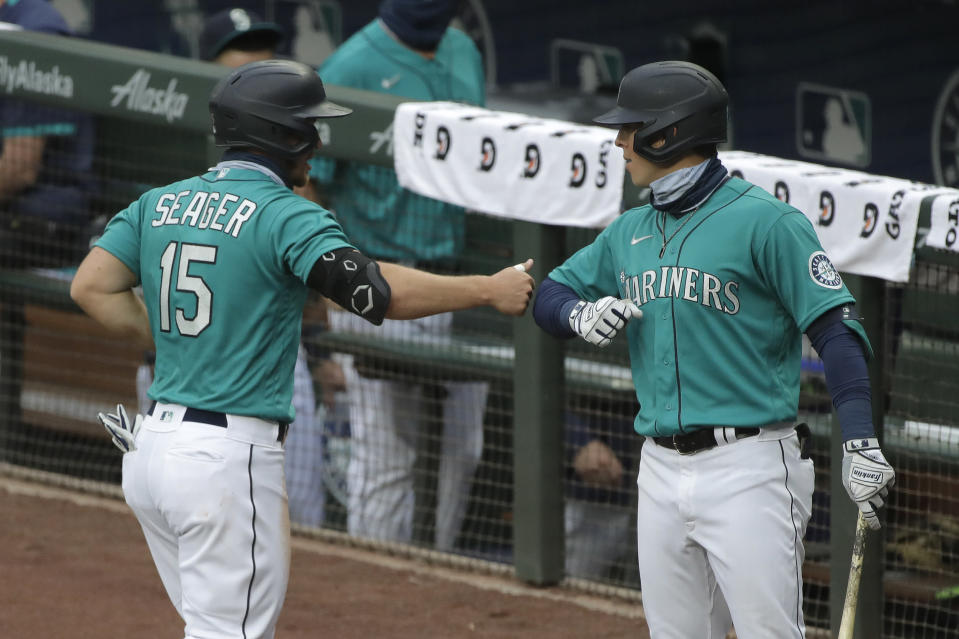 Seattle Mariners' Kyle Seager, left, greets Dylan Moore, right, after scoring against the Oakland Athletics during the fourth inning of a baseball game Friday, July 31, 2020, in Seattle. (AP Photo/Ted S. Warren)