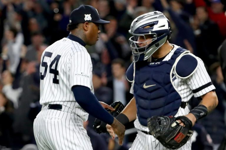 Aroldis Chapman (L) of the New York Yankees celebrates with teammate Gary Sanchez after defeating the Houston Astros in Game Four of the American League Championship Series, at Yankee Stadium in New York, on October 17, 2017