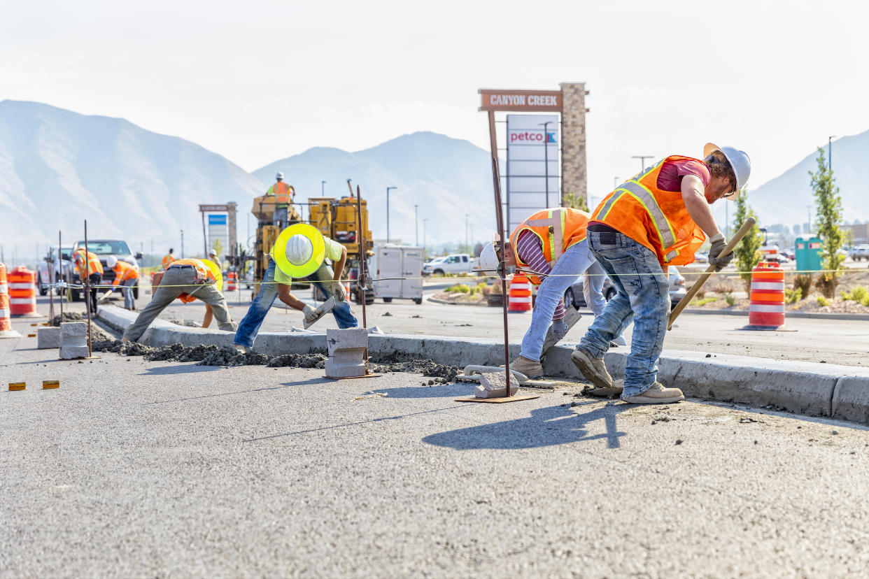 Spanish Fork, UT, USA – August 3, 2017: Road construction worker scoups up concrete while cleaning up a center medium just laid in Spanish Fork, Utah. Other workers smooth out the center medium with a float