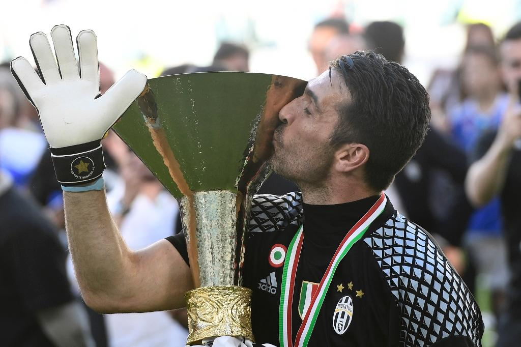 "Juventus' goalkeeper from Italy Gianluigi Buffon kisses the trophy after winning the Italian Serie A football match Juventus vs Crotone and the ""Scudetto"" at the Juventus Stadium in Turin on May 21, 2017 (AFP Photo/MIGUEL MEDINA)"