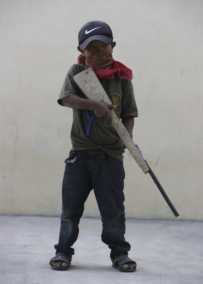 A child holds a fake, wooden rifle during a display for the media designed to attract the federal government's attention to the dangers of organized crime his town negotiates daily in Ayahualtempa, Guerrero state, Mexico, Wednesday, April 28, 2021. Most of the youths who participate are the children of the town's community police force, essentially vigilantes who guard the entrances to the town with old shotguns. (AP Photo/Marco Ugarte)