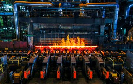 A red-hot steel plate passes through a press at the ArcelorMittal steel plant in Ghent