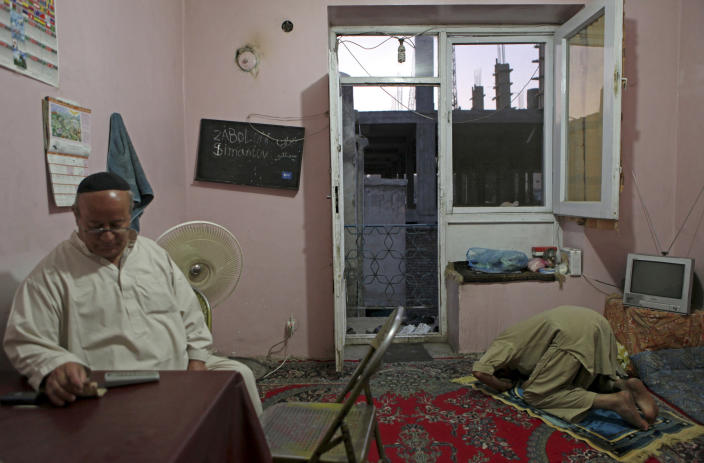 In this photo taken Saturday, Aug. 29, 2009, Zebulon Simentov, left, the last known Jew living in Afghanistan and the caretaker and sole member of Afghanistan's only working synagogue, sits at as his dining room table during Shabbat in his Kabul home, as Shirgul Amiri, a local Muslim friend, prays. Simentov who prayed in Hebrew, endured decades of war as the country's centuries-old Jewish community rapidly dwindled has left the country. The Taliban takeover in August, 2021, seems to have been the last straw. (AP Photo/David Goldman, File)