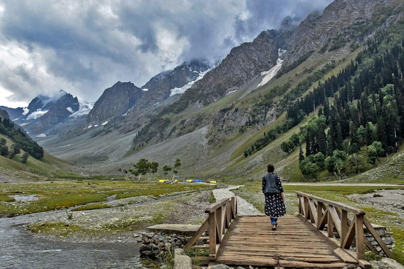 JAMMU AND KASHMIR, INDIA - 2019/07/28: A visitor walks through a foot bridge on a cloudy day at the tourist resort Sonamarg about 90kms from Srinagar, the summer capital of J&K, India. As the rains continued for the fourth day on Sunday, the skies remained cloudy in the second half of the day. The weather department has predicted more precipitation in many parts of the valley in the next 24 hours. (Photo by Saqib Majeed/SOPA Images/LightRocket via Getty Images)
