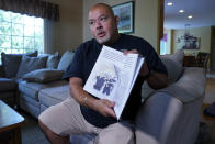 """Will Jimeno, the former Port Authority police officer who was rescued from the rubble of the Sept. 11, 2001 attacks at the World Trader Center after many hours, holds the children's book he wrote, """"Immigrant, American, Survivor,"""" that draws on his experience, during an interview at his home in Chester, N.J., Monday, Aug. 2, 2021. (AP Photo/Richard Drew)"""