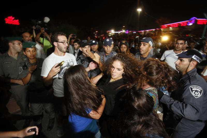 Isaeli supporters of the Organization for Prevention of Assimilation in the Holy Land (LEHAVA) scuffle with police during a demonstration against the wedding of Mahmoud Mansour and Morel Malcha, on August 17, 2014 in Rishon Letzion (AFP Photo/Gali Tibbon)