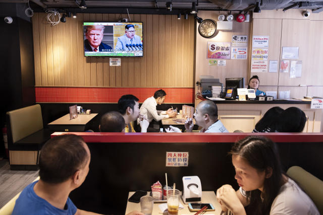<p>At a restaurant in Hong Kong, a TV screen shows President Trump and North Korea leader Kim Jong Un on Tuesday. (Photo: Miguel Candela/SOPA Images/LightRocket via Getty Images) </p>