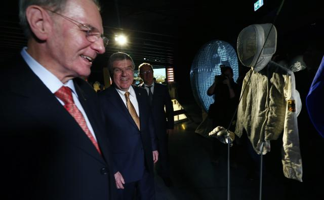 International Olympic Committee (IOC) President Thomas Bach (2nd L) poses next to his predecessor Jacques Rogge in front of Bach's fencing outfit for the Montreal 1976 Olympics at the Olympic Museum in Lausanne December 10, 2013. REUTERS/Denis Balibouse (SWITZERLAND - Tags: SPORT OLYMPICS)