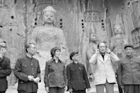 Canadian prime minister Pierre Elliott Trudeau jokes around in front of huge Buddhas at the Lungmen Caves on Oct. 14, 1973, Bettmann/Getty Images