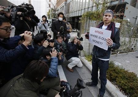 Kolin Burges (R), a self-styled cryptocurrency trader and former software engineer from London, holds a placard to protest against Mt. Gox, as photographers take photos of him in front of the building where the digital marketplace operator is housed in Tokyo February 26, 2014. REUTERS/Toru Hanai