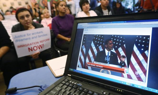 President Obama's speech on immigration is played on a computer screen during a watch party, in New York, Jan. 29.