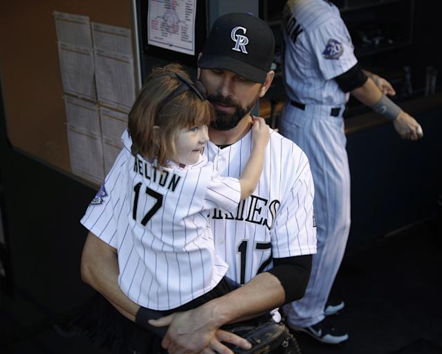 Before playing in his final home game, Colorado Rockies first baseman Todd Helton holds his daughter Gentry Grace in the dugout to take her to a ceremony to mark his upcoming retirement before Helton and his teammates faced the Boston Red Sox in a baseball game in Denver on Wednesday, Sept. 25, 2013. (AP Photo/David Zalubowski)