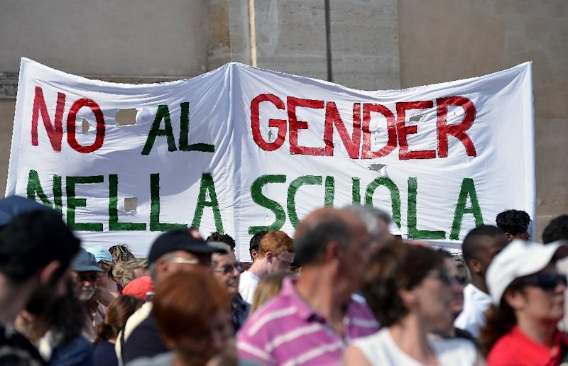 """People hold a banner that reads """" No gender in school"""" during a rally against gay unions and the teaching of gender theories in schools in Rome's San Giovanni square on June 20, 2015 (AFP Photo/Tiziana Fabi)"""