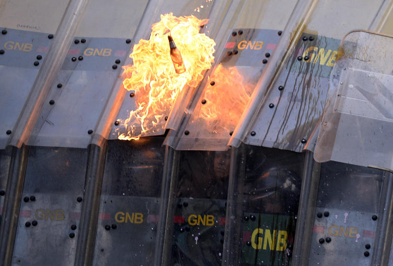 Riot police take cover as a Molotov cocktail is thrown at them during an anti-government protest in Caracas on February 28, 2014