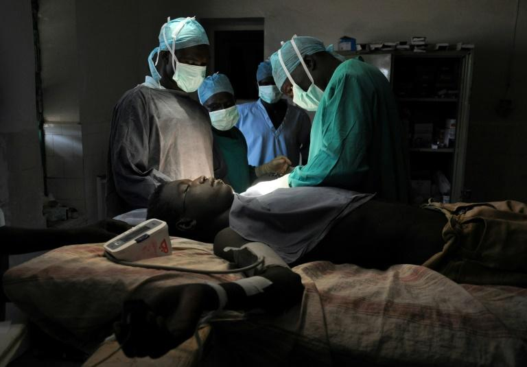 Doctor Evan Atar Adaha and his team perform nearly 60 surgeries per week in a room with just one light