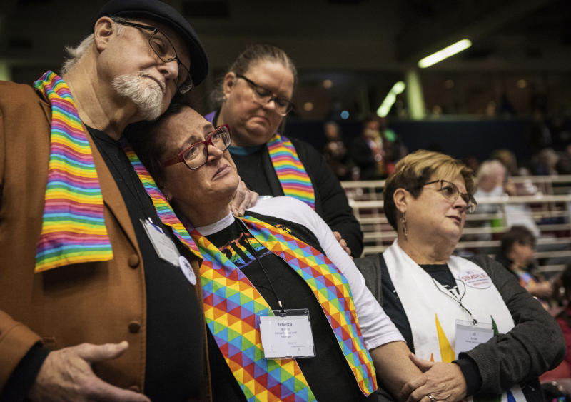 FILE - In this Feb. 26, 2019, file photo, Ed Rowe, left, Rebecca Wilson, Robin Hager and Jill Zundel, react to the defeat of a proposal that would allow LGBTQ clergy and same-sex marriage within the United Methodist Church at the denomination's 2019 Special Session of the General Conference in St. Louis, Mo. Had there been no COVID-19 coronavirus pandemic, America's largest mainline Protestant denomination would be convening in May 2020 for a likely vote on breaking up over differences on same-sex marriage and ordination of LGBTQ pastors. (AP Photo/Sid Hastings, File)